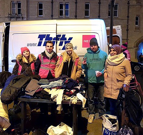 The Pass It On team with clothes for the homeless